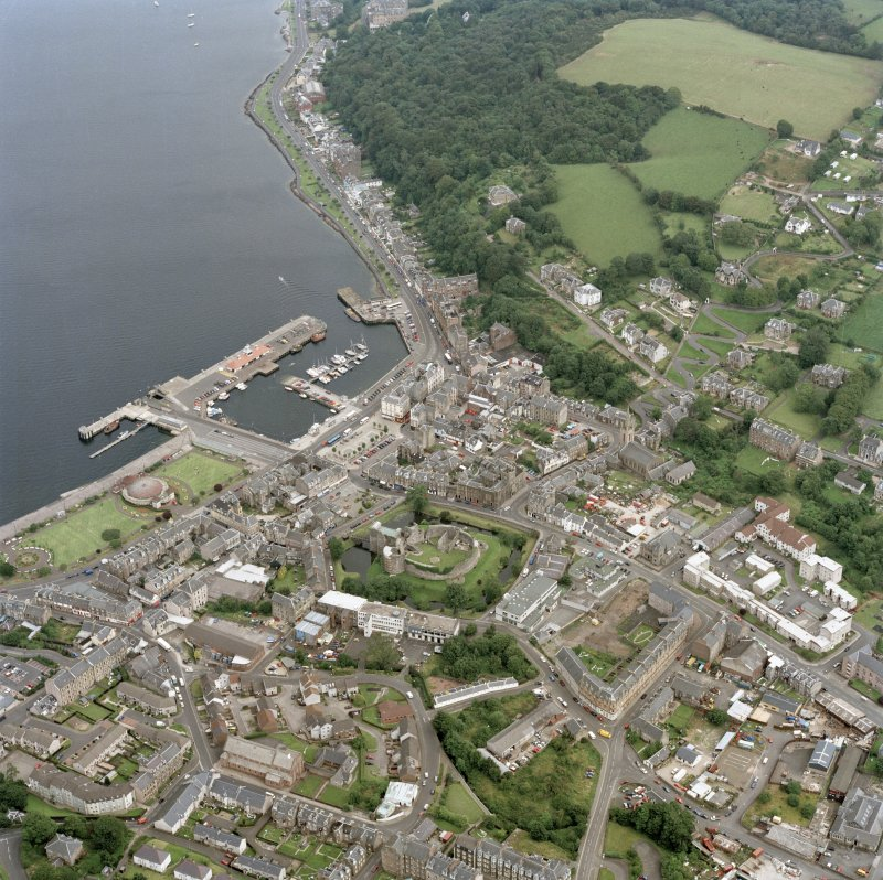General oblique aerial view of Rothesay centred on the remains of the castle, the harbour and winter gardens, taken from the WSW.