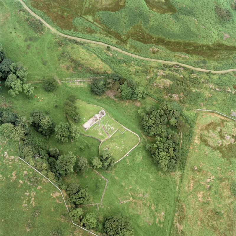 Oblique aerial view centred on the remains of the burial-ground and church, taken from the SW.