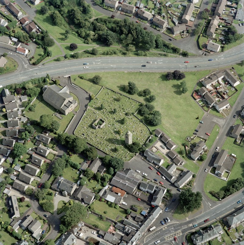 Oblique aerial view centred on the burial ground, belfry and clock tower with St Ninian's Church and manse adjacent, taken from the NW.