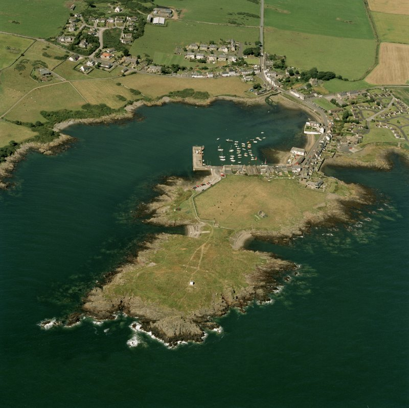 Oblique aerial view centred on the village, harbour, and the remains of the chapel and promontory fort, taken from the ESE.