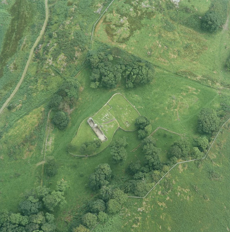 Oblique aerial view centred on the remains of the burial-ground and church, taken from the WNW.