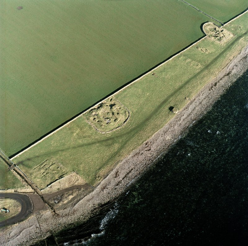 Oblique aerial view of the remains of the brochs, buildings, possible building, pillbox and slipway, Keiss, taken from the S.