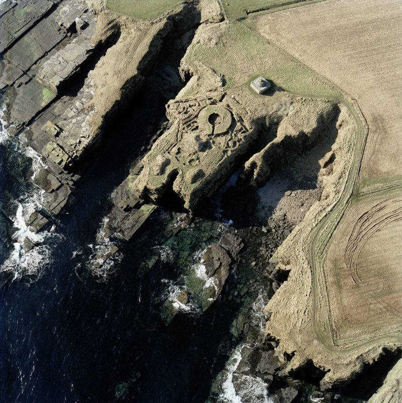 Oblique aerial view of the commemorative monument and the remains of the broch, Nybster, taken from the NE.