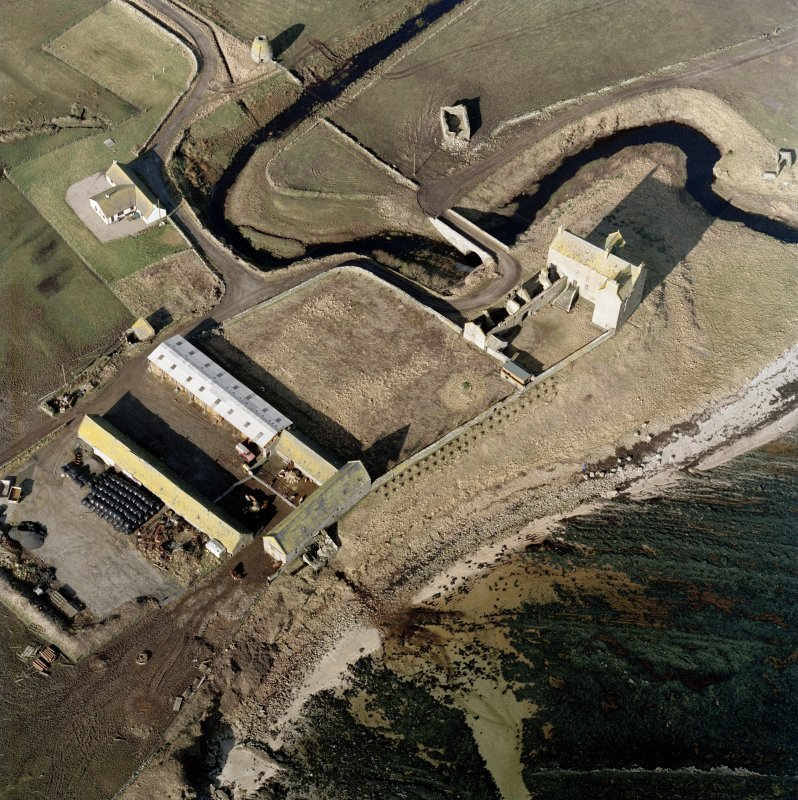 Oblique aerial view of Freswick castle, bridge, farmsteading and the remains of the mausoleum, dovecot and anti-tank blocks, taken from the E.