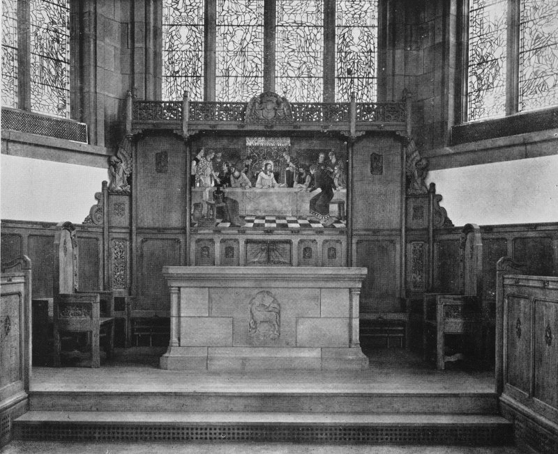 Copy of photograph showing altar and reredos showing Last Supper, Agnus Dei (Lamb of God) and angels supporting shield (coat of arms).