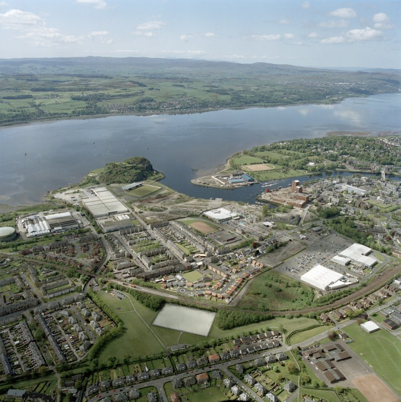 General oblique aerial view of Dumbarton looking across the works, football ground, castle, whisky distillery and the River Clyde towards Langbank, taken from the NE.