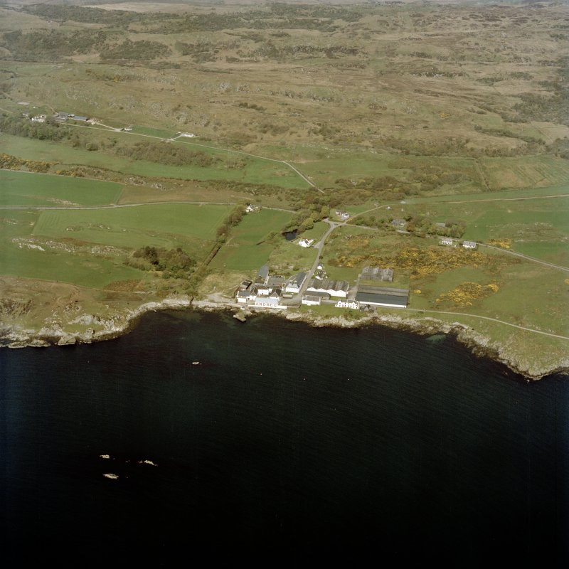 Oblique aerial view centred on the whisky distillery and pier, taken from the SE.