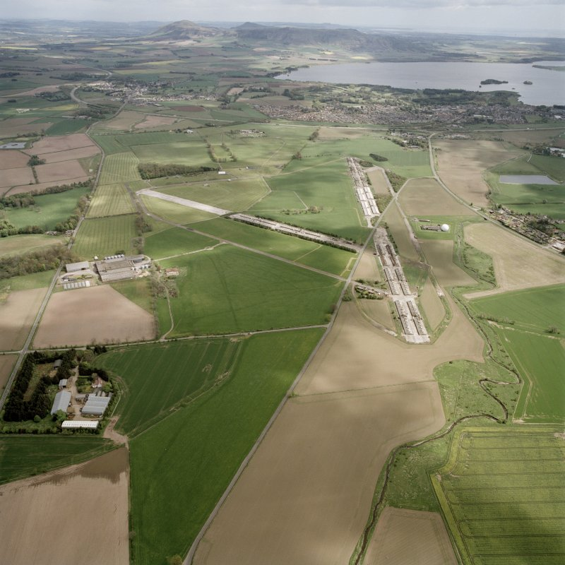 Oblique aerial view looking across the farmsteading, airfield and radio station towards Kinross, taken from the W.