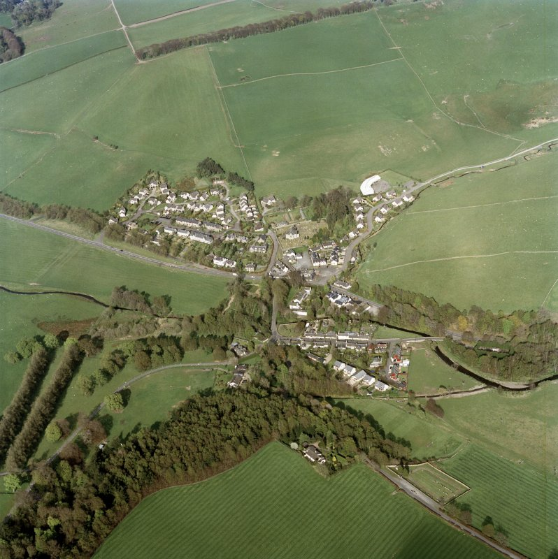 Oblique aerial view of Eddleston centred on the church and churchyard, taken from the W.