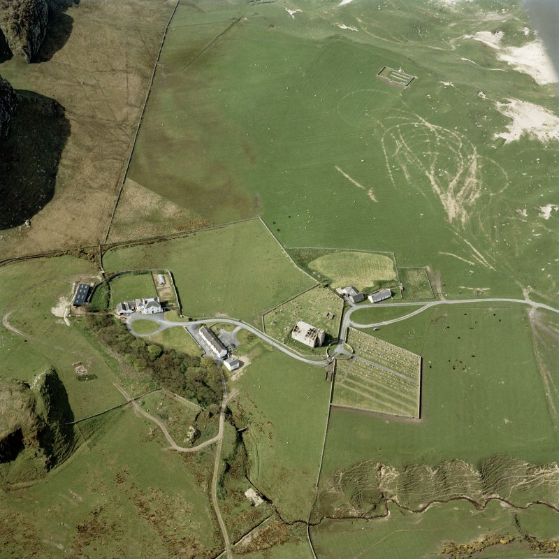 Oblique aerial view of Kilchoman centred on the church, burial-grounds and manse, taken from the NE.