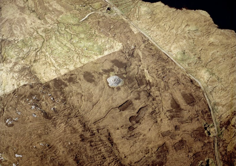 Oblique aerial view centred on the remains of the chambered cairn, taken from the SE.