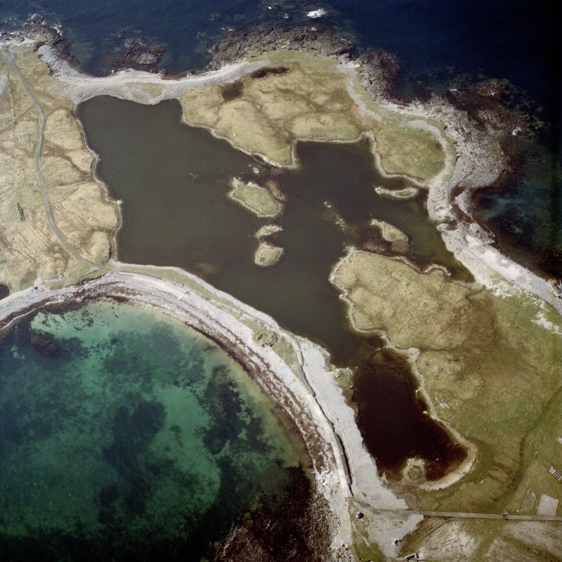 Oblique aerial view centred on the remains of the dun, taken from the SE.