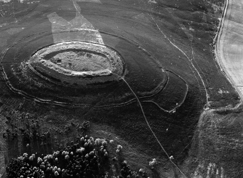 Oblique aerial view centred on the cropmarks of roundhouses  and a rectangular enclosure within the White Caterthun fort with the remains of an unenclosed settlement adjacent, looking to the NW.