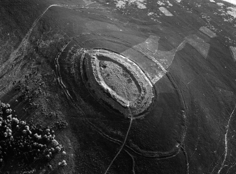 Oblique aerial view centred on the cropmarks of roundhouses  and a rectangular enclosure within the White Caterthun fort with the remains of an unenclosed settlement adjacent, looking to the S.