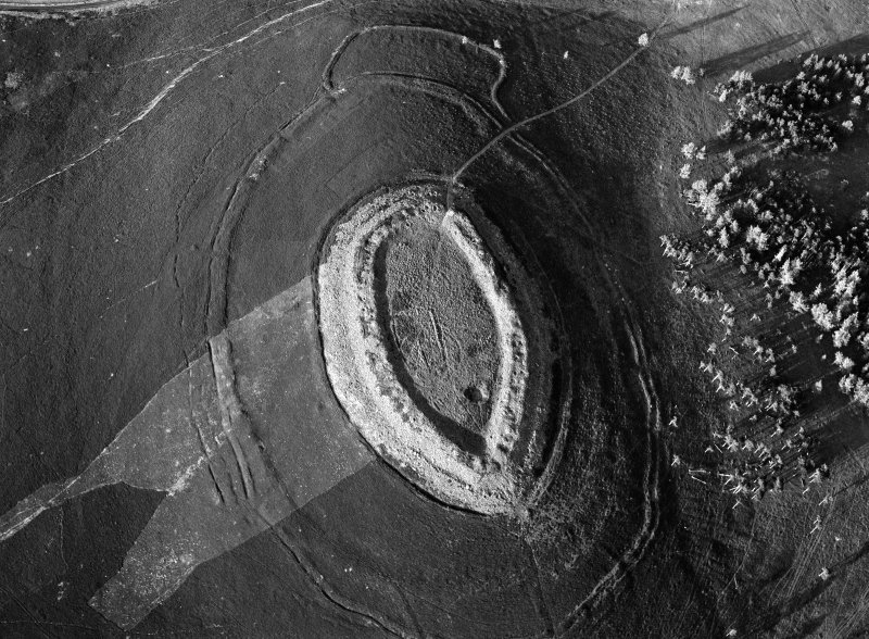 Oblique aerial view centred on the cropmarks of roundhouses  and a rectangular enclosure within the White Caterthun fort with the remains of an unenclosed settlement adjacent, looking to the NNE.