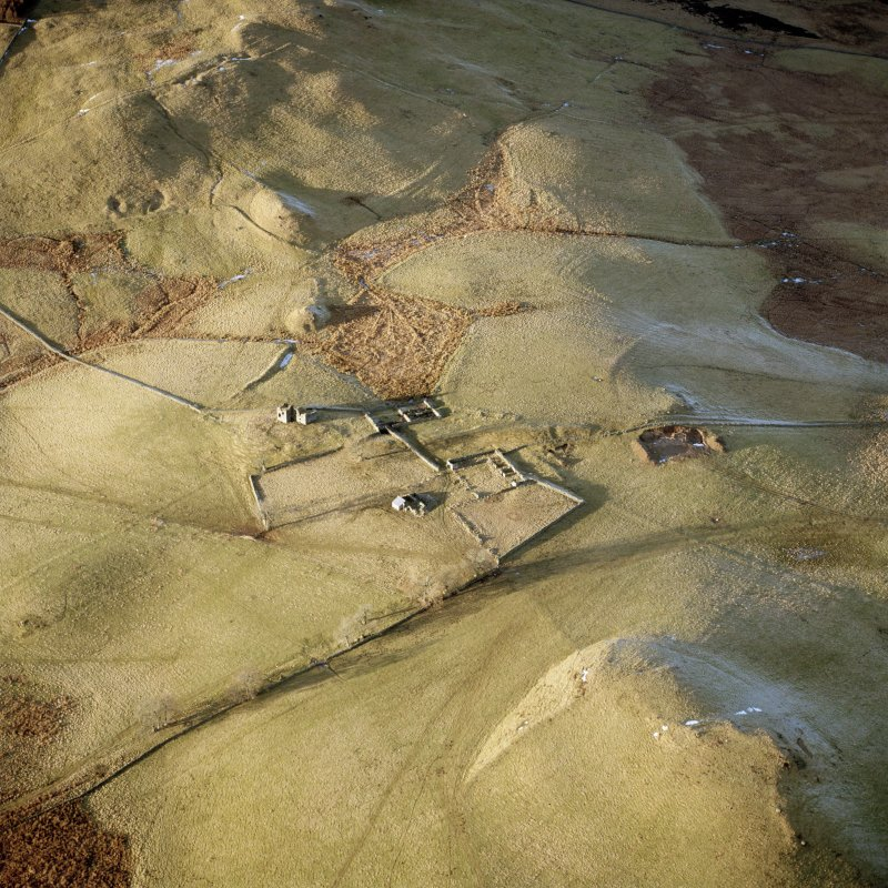 Scanned image of oblique aerial view centred on the remains of the farmstead, buildings and tower-house, with the remains of the farmstead adjacent, taken from the SSE.