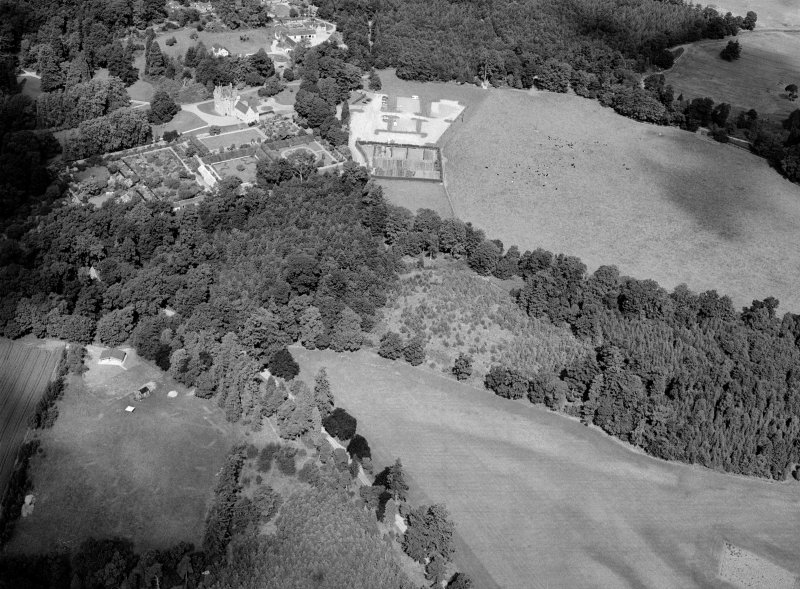 Oblique aerial view centred on the cropmarks of the pit alignment and timber hall with Crathes Castle and gardens adjacent, looking to the NW.