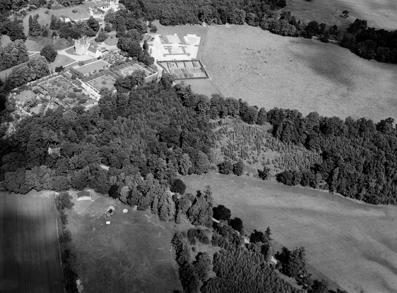 Oblique aerial view centred on the cropmarks of the pit alignment and timber hall with Crathes Castle and gardens adjacent, looking to the NNW.
