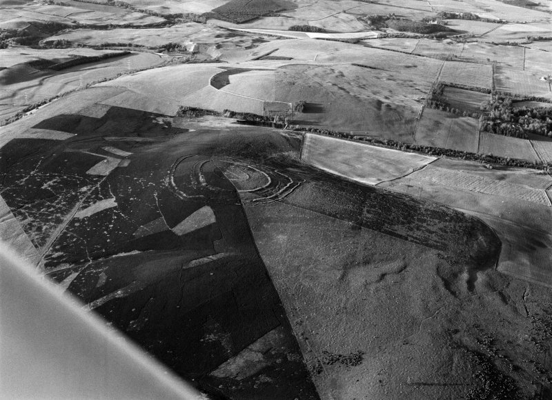 Oblique aerial view centred on the remains of Brown Caterthun fort, looking to the NNE.