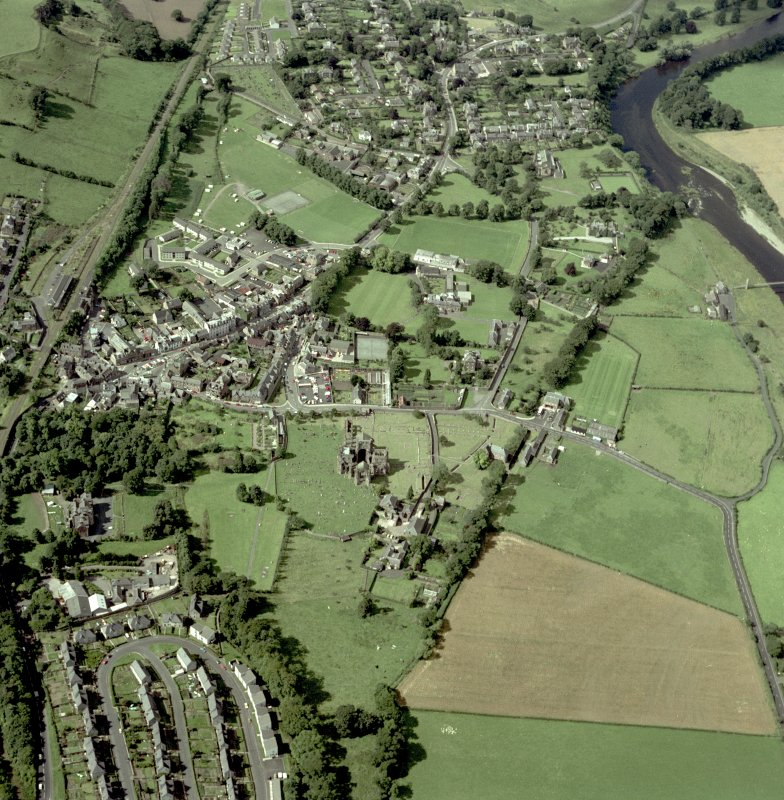 Oblique aerial view centred on abbey from E.
