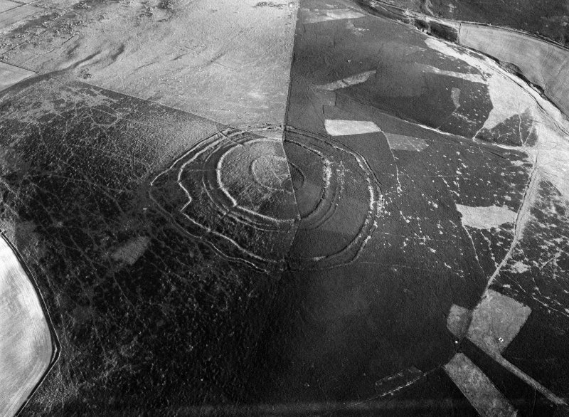 Oblique aerial view centred on the remains of Brown Caterthun fort, looking to the SSW.