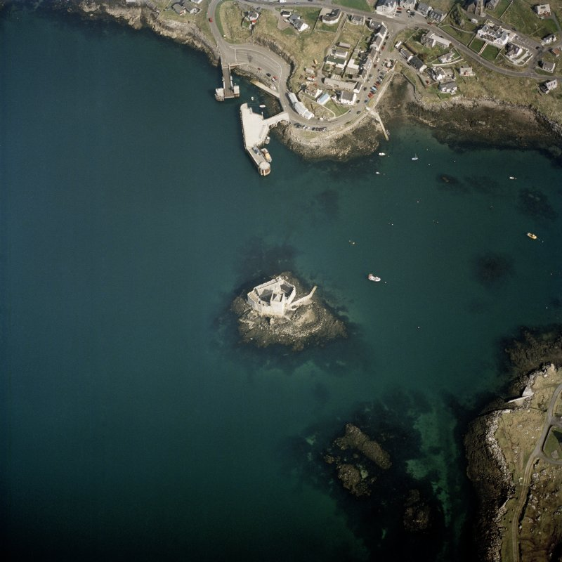 Oblique aerial view centred on the tower-house with the pier and town adjacent, taken from the S.
