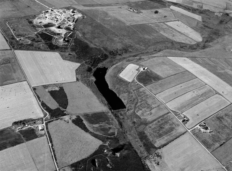 Oblique aerial view centred on the Den of Boddam reservoir, flint mines and lithic working site with RAF Buchan radar station adjacent, looking to the SSW.