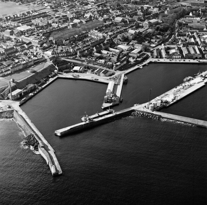 Oblique aerial view centred on the harbour with the town adjacent, taken from the NE.