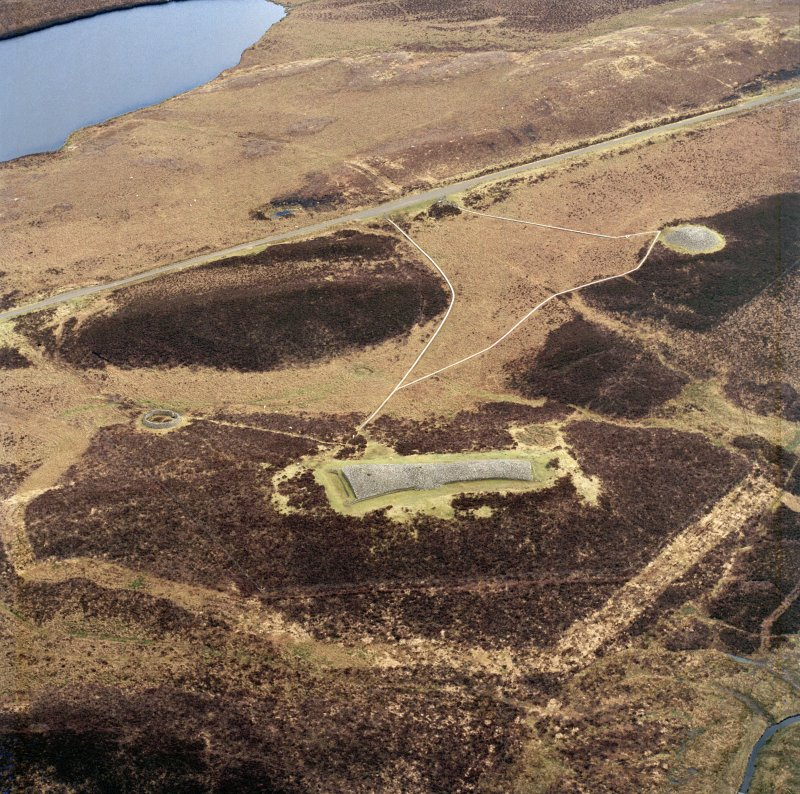 Oblique aerial view centred on the remains of the chambered  cairns, taken from the WNW.
