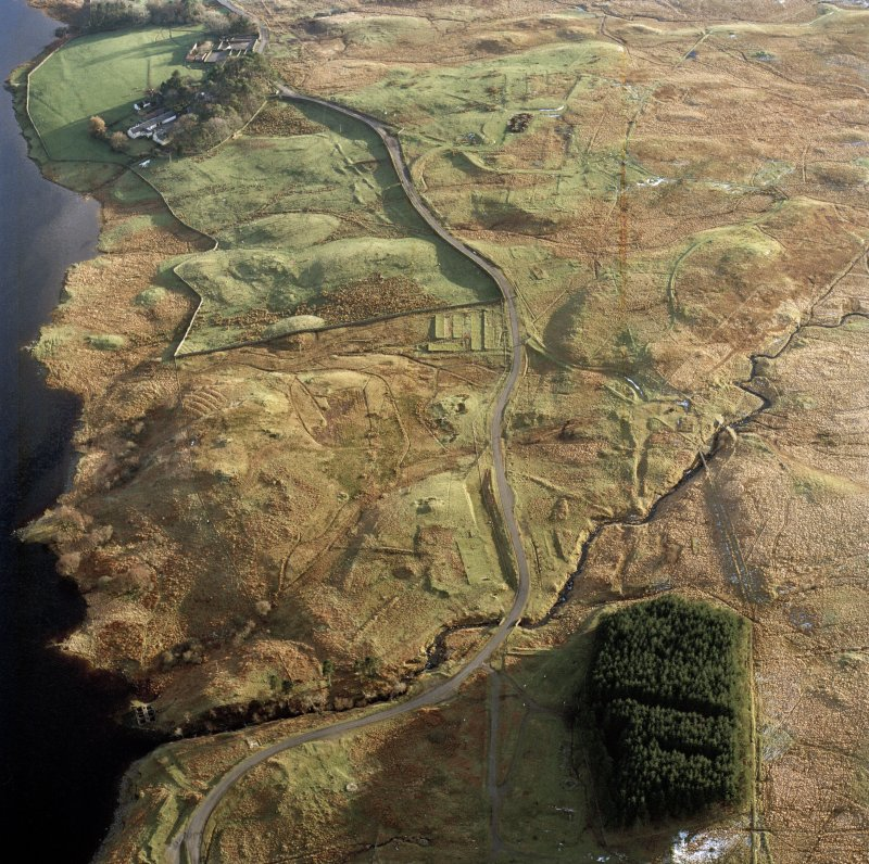 Oblique aerial view centred on the remains of the Loch Doon aerial gunnery school military camp with the farmsteading and sheepfold adjacent, taken from the N.