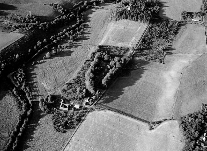 Oblique aerial view centred on the remains of the chambered cairns at Balnuaran of Clava with the farmstead adjacent, looking to the NE.