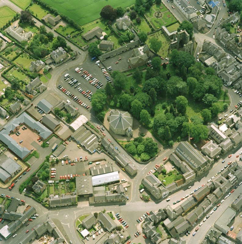 Oblique aerial view centred on the church, taken from the N.  Also visible is Kelso Abbey.