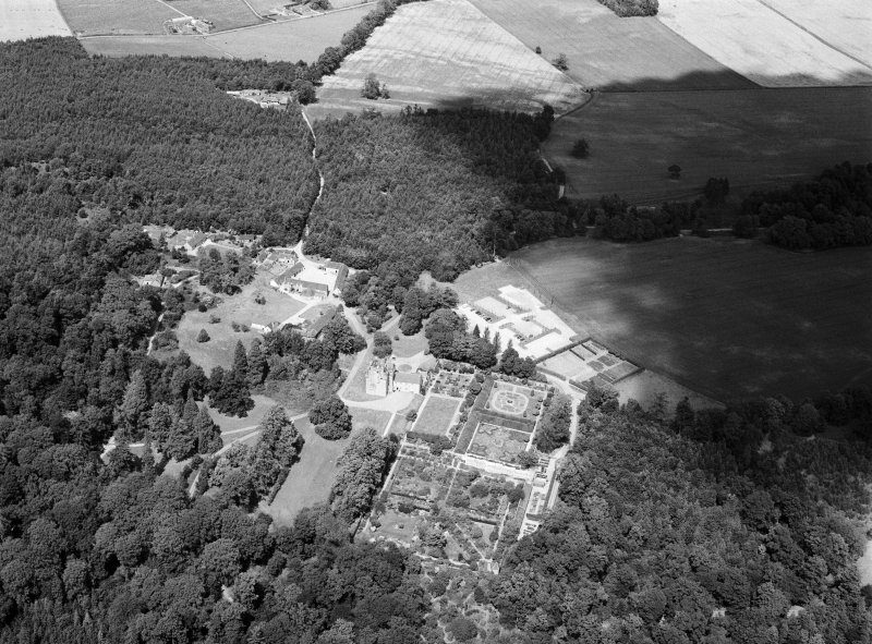 Oblique aerial view centred on Crathes Castle and gardens with the cropmarks of the pit alignment and timber hall adjacent, looking to the NNE.