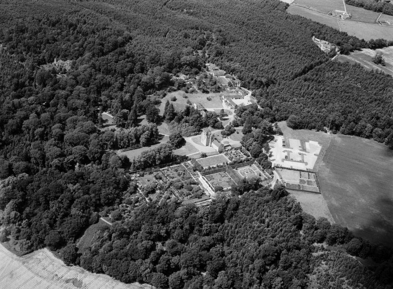 Oblique aerial view centred on Crathes Castle and gardens with the cropmarks of the pit alignment and timber hall adjacent, looking to the NNW.
