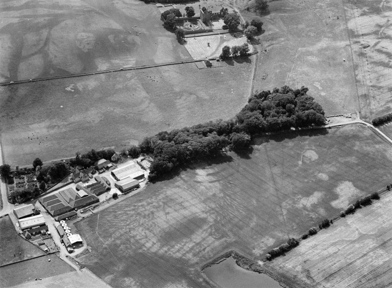 Oblique aerial view centred on the cropmarks of the fort, ring ditch and rig at Mains of Edzell with the farmstead adjacent, looking to the W.