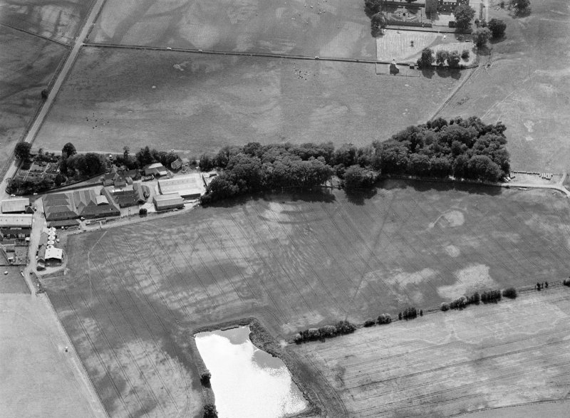 Oblique aerial view centred on the cropmarks of the fort, ring ditch and rig at Mains of Edzell with the farmstead adjacent, looking to the SW.