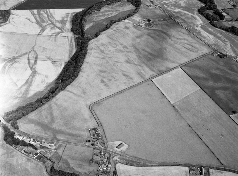 Oblique aerial view centred on the cropmarks of the pit defined cursus, unenclosed settlement, ring ditches, enclosures, pits and rig with Stracathro Roman Fort and Temporary Camp adjacent at Inchbare North, looking to the ENE.