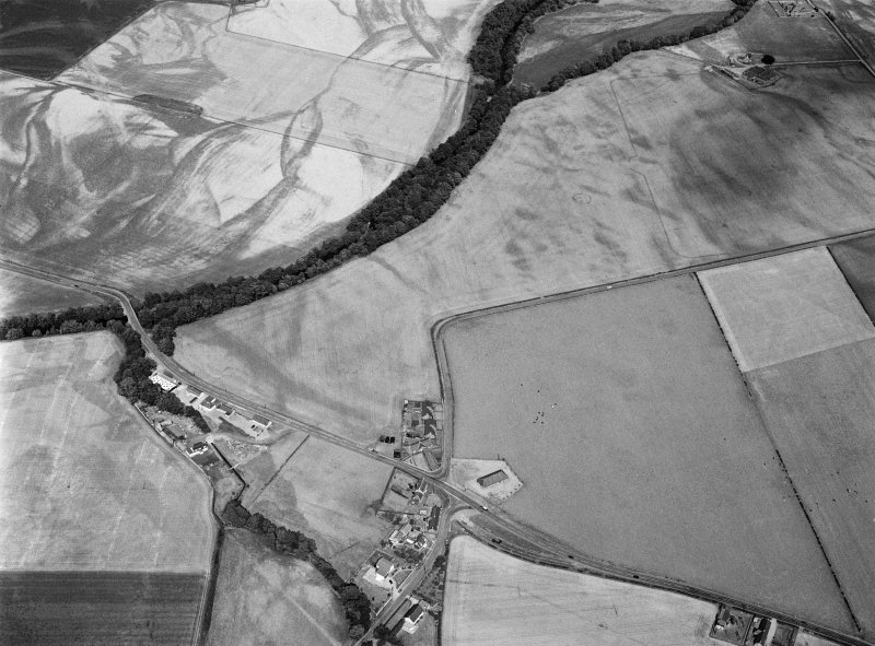 Oblique aerial view centred on the cropmarks of the pit defined cursus, unenclosed settlement, ring ditches, pits and rig with Stracathro Roman Fort and Temporary Camp adjacent at Inchbare North, looking to the NE.