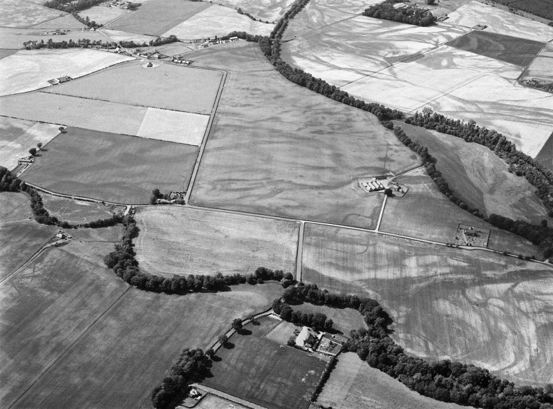 Oblique aerial view centred on the cropmarks of the unenclosed settlement, ring ditches, pits and rig with Stracathro Roman Fort and Temporary Camp adjacent at Smiddyhill, looking to the WNW.