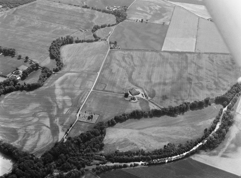 Oblique aerial view centred on the cropmarks of the unenclosed settlement, ring ditches, pits and rig with Stracathro Roman Fort and Temporary Camp adjacent at Smiddyhill, looking to the SW.