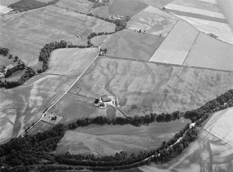 Oblique aerial view centred on the cropmarks of the unenclosed settlement, ring ditches, pits and rig with Stracathro Roman Fort and Temporary Camp adjacent at Smiddyhill, looking to the SSW.