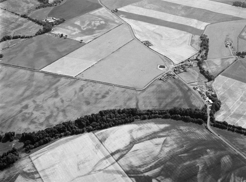 Oblique aerial view centred on the cropmarks of the unenclosed settlement, ring ditches, pits and rig with Stracathro Roman Fort and Temporary Camp adjacent at Smiddyhill, looking to the S.
