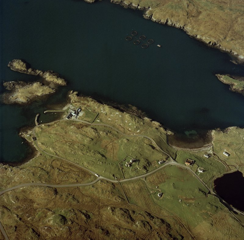 Oblique aerial view centred on the church and burial ground and the remains of the military camp with the hotel and remains of the boat nausts adjacent, taken from the NE.