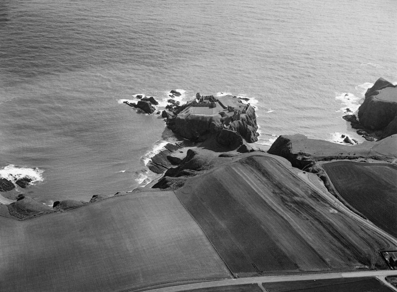 Oblique aerial view centred on the remains of the earthwork and castle at Dunnottar, looking to the ESE.