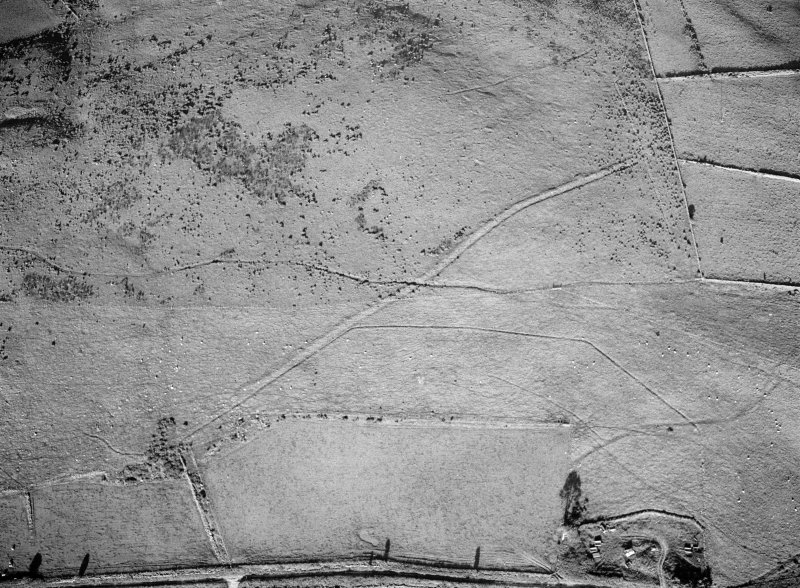 Oblique aerial view centred on the remains of the Roman temporary camp and cairnfield at Raedykes and Garrison Hill, looking to the E.