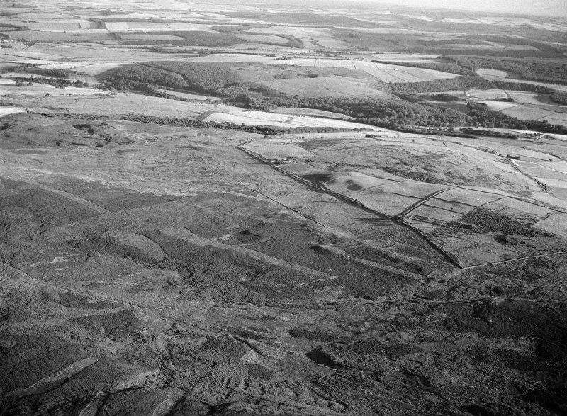 Distant oblique aerial view centred on the remains of the Roman temporary camp and cairnfield at Raedykes and Garrison Hill, looking to the SSW.