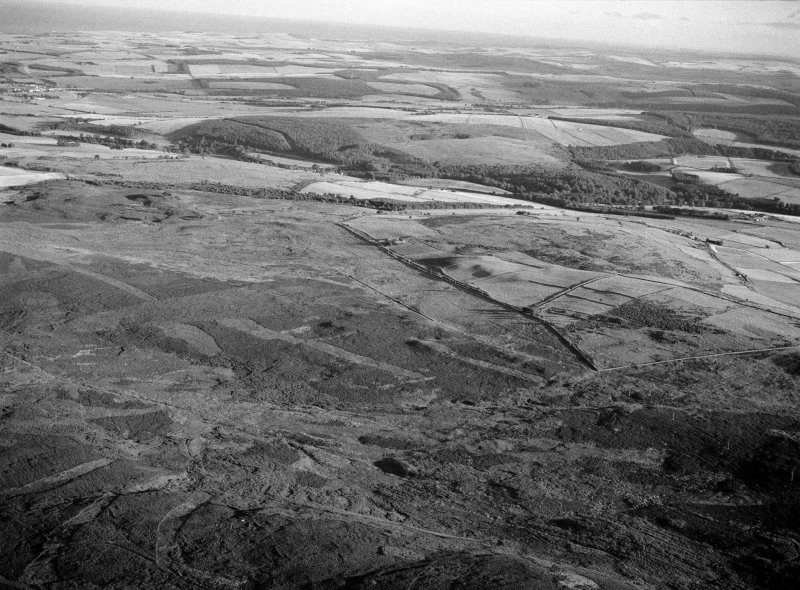Oblique aerial view centred on the remains of the Roman temporary camp and cairnfield at Raedykes and Garrison Hill, looking to the SSW.