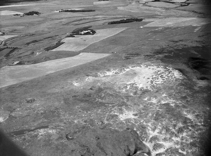 Oblique aerial view centred on the remains of hut circles, ring cairn and the midden at Sands of Forvie, looking to the NW.