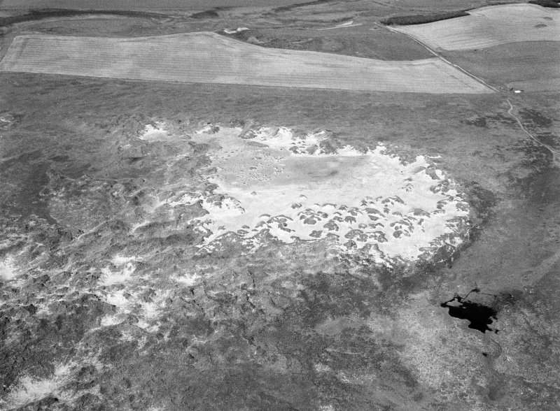 Oblique aerial view centred on the remains of hut circles, ring cairn and the midden at Sands of Forvie, looking to the WNW.