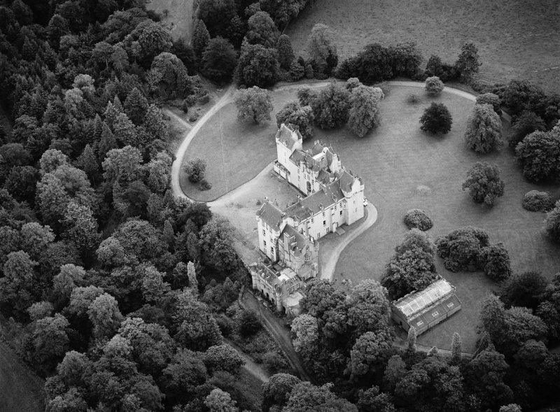 Oblique aerial view centred on Fyvie Castle with the racquets court adjacent, looking to the SSE.